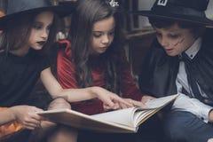 三个孩子坐地板并且读咒语旧书为万圣夜 免版税库存照片