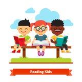 三个孩子坐长凳和阅读书 免版税库存图片