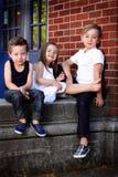 三个孩子坐 库存图片