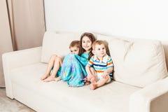 三个孩子是在长沙发的被拍摄的开会 免版税库存照片