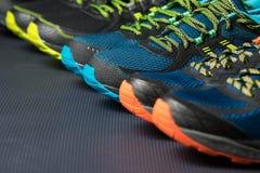 三个对五颜六色的连续教练员/锻炼鞋子在体育/鞋店的地板上 免版税库存图片