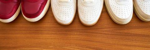 三个对在一张木表面顶视图的红色和白色运动鞋鞋子 免版税库存图片