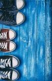 三个对在蓝色被佩带的木背景的老运动鞋 免版税图库摄影