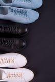 三个对在黑背景的运动鞋 黑,白色和蓝色鞋子 顶视图 复制空间 免版税库存照片