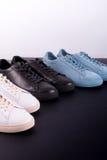 三个对在黑背景的运动鞋 黑,白色和蓝色鞋子 免版税库存照片