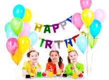 三个小女孩获得乐趣在生日聚会 免版税图库摄影