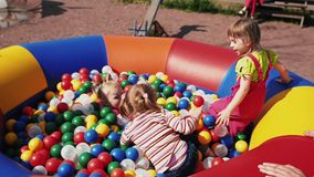 三个小女孩跳对于儿童绷床充满颜色球 fest 股票视频