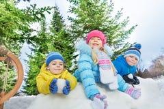 三个小孩戏剧雪球战斗 免版税库存图片