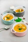 三个小服务罐或碗用奶油色汤由红色小扁豆制成用面包干、香料和草本荷兰芹,香菜 库存图片