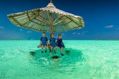 三个小男孩在沙滩伞在海洋,热带Ma下 免版税库存图片
