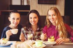 三个少妇在一次会议上在咖啡馆 免版税图库摄影
