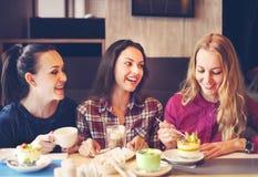 三个少妇在一次会议上在咖啡馆 库存照片