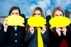 三个少妇在手上的拿着一块黄色板材 库存图片