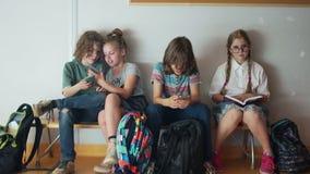 三个少年是热情关于他们的电话 最佳的学生读坐在他们旁边的一本书 学生和 影视素材