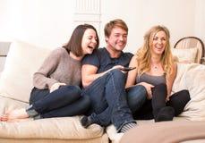 三个少年享受一个滑稽的电视节目 免版税库存照片