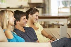 三个少年在家坐沙发使用片剂计算机和膝上型计算机,看电视 库存图片
