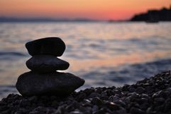 三个岩石剪影在海滩的 免版税库存图片