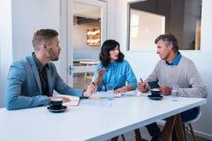 三个工作同事一起谈事务在办公室 免版税库存图片