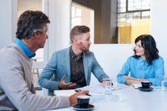 三个工友开战略会议在一个现代办公室 免版税库存图片