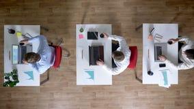 三个年轻人商人研究膝上型计算机,同时喝咖啡,工作概念,办公室概念,通信 股票录像