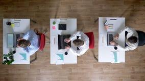 三个年轻人商人研究膝上型计算机,同时离开工作场所,工作概念,办公室概念 股票视频