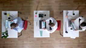 三个年轻人商人研究膝上型计算机,同时观看图,工作概念,办公室概念 股票视频