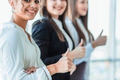 三个年轻企业女孩在办公室 穿戴在经典衣物样式,显示赞许 免版税库存图片