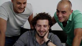 三个年轻可爱的人看膝上型计算机和快乐一起笑 影视素材