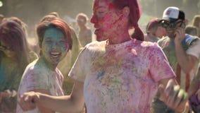 三个年轻愉快的不同种族的女朋友在holi节日跳舞自白天在夏天,友谊概念 股票视频