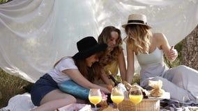 三个年轻有吸引力的女孩纸牌比赛前面英尺长度  野餐, bachelorette概念 户外,白色布料 影视素材