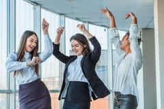 三个年轻美丽的深色的企业夫人在办公室 所有愉快的跳舞的跳舞与拷贝空间 库存照片