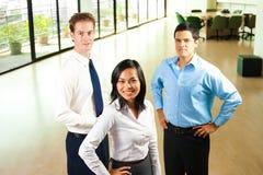 三个微笑的同事办公室 免版税库存图片