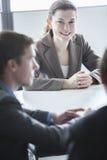三个微笑的商人坐在桌上和开业务会议在办公室 库存照片
