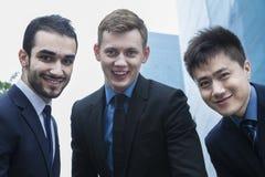 三个微笑的商人画象,户外,商业区 免版税图库摄影