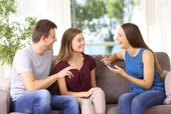 三个快乐的朋友在家谈话在长沙发 免版税库存图片