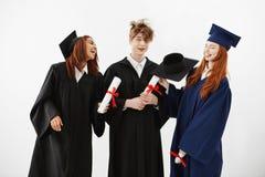 三个快乐的毕业生微笑的讲的唬弄拿着在胁迫和取笑的白色背景的文凭 库存图片
