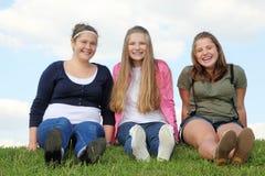 三个愉快的女孩坐在草 免版税库存图片