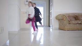 三个愉快的孩子打开门和奔跑在大轻的室里面 使用在房子里的男孩和两个女孩 休闲  影视素材