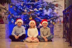 三个愉快的孩子画象获得乐趣在圣诞前夕 免版税库存图片