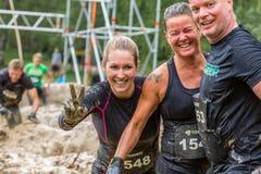 三个愉快的泥泞的赛跑者 库存照片