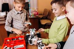三个愉快的男孩在机器人学学校做机器人 免版税库存图片