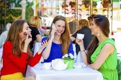 三个愉快的美丽的女孩女朋友饮用的茶在一个夏天 免版税库存照片