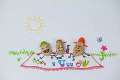 三个愉快的花生小雕象有野餐在一个晴天 免版税库存图片