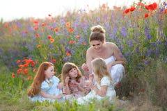 三个愉快的年轻女儿和母亲有野餐在夏天p 免版税库存照片
