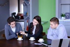 三个成功的同事、女孩和两个人总结工作  库存图片
