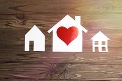 三个房子由与心脏的纸制成在木背景塑造 住房,家庭的概念 库存图片