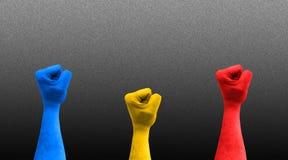 三个拳头在与罗马尼亚旗子颜色的天空中 免版税库存照片