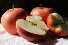 三个新鲜的红色苹果和他们中的一个由一半分裂 免版税库存图片