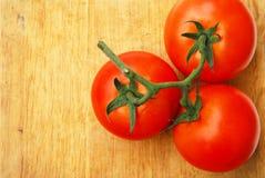 三个新鲜的蕃茄是红色和绿色果子终端 免版税库存照片
