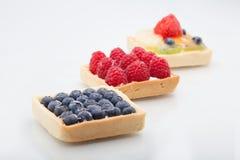 三个方形的蛋糕排队了对角地用草莓, raspbe 免版税库存图片